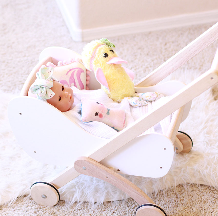 all her favorite 'babies' go into the doll pram | the love designed life