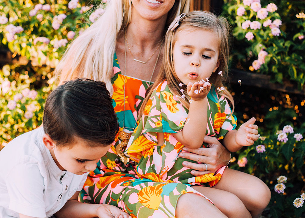 blowing flower petals to make a wish in matching mommy and me outfits | thelovedesignedlife.com