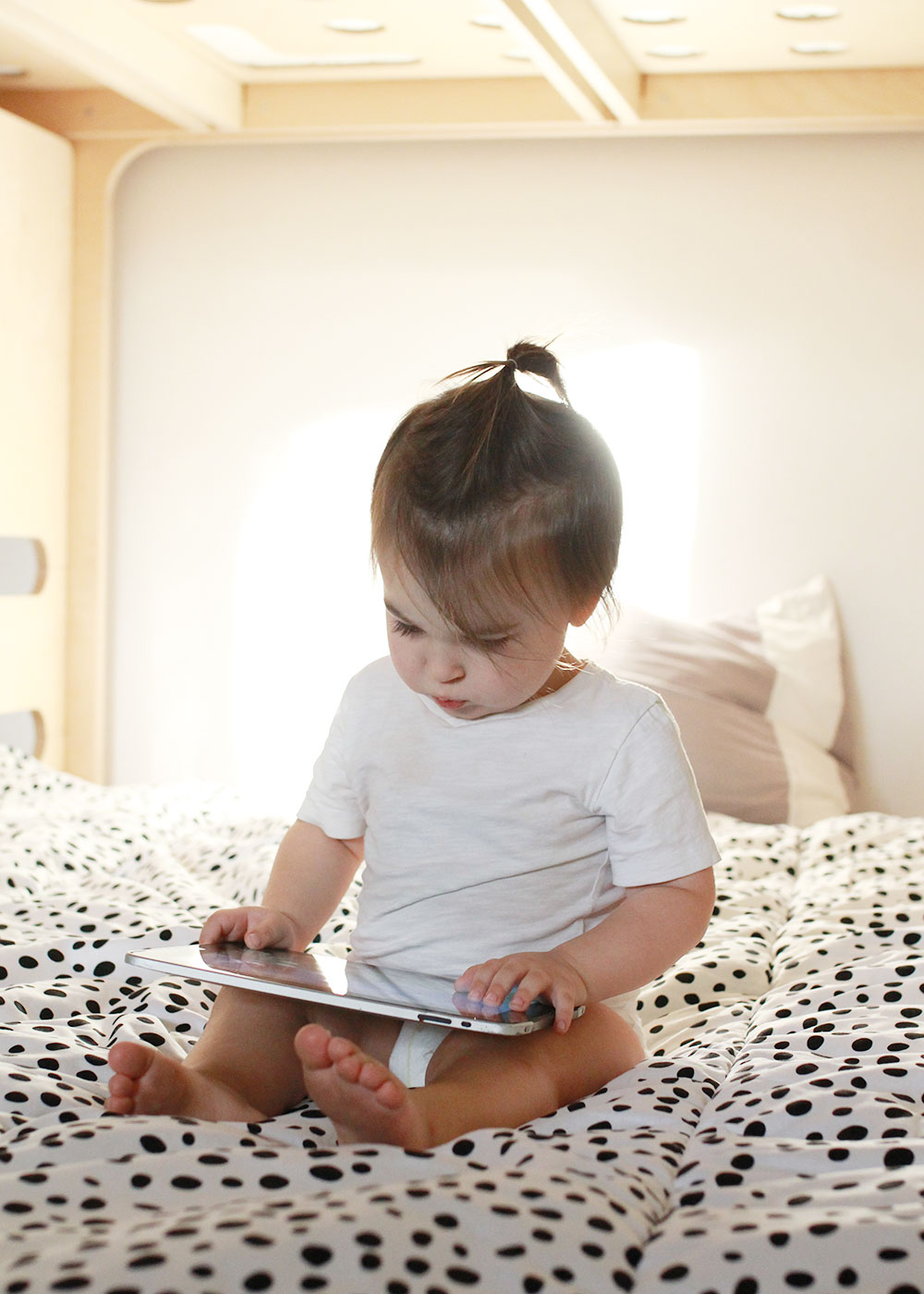 sweet boy checking out his big boy bed with the ipad and internet | thelovedesignedlife.com