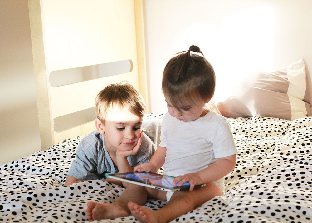 love these brothers watching their ipad in their new bunk beds | thelovedesignedlife.com