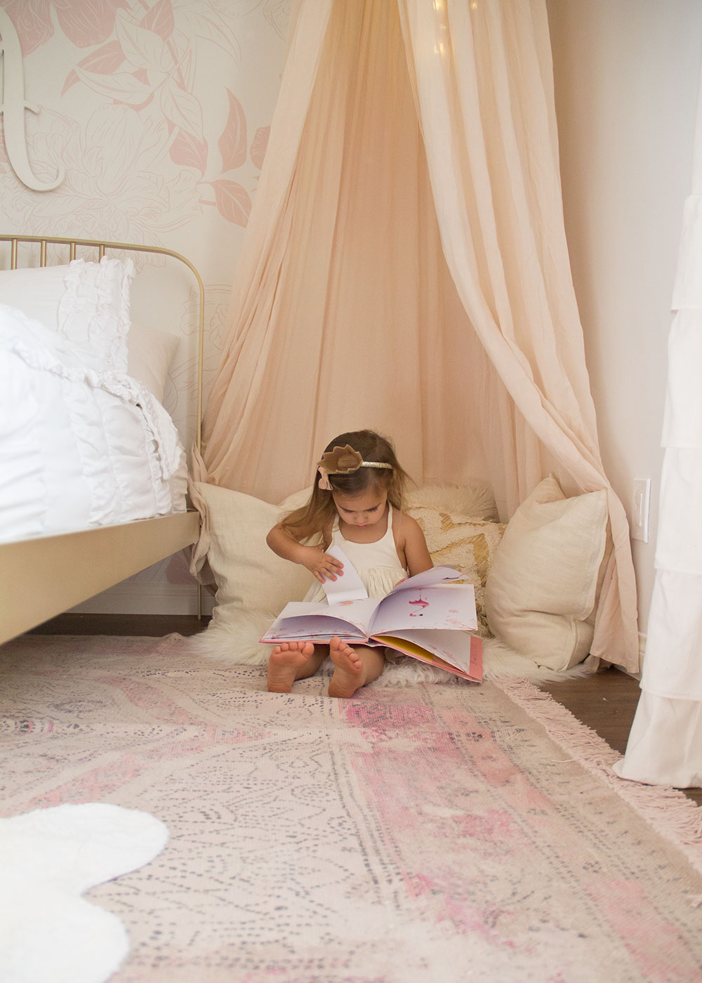 she loves her special little reading nook in her new pink and gold big girl's room | thelovedesignedlife.com