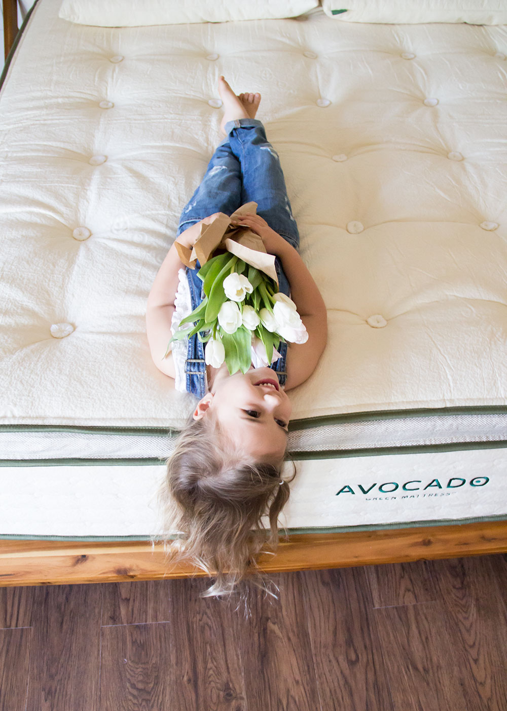 my sweet little girl holding her tulips on our new avocado green mattress. my review here! | thelovedesignedlife.com #tulips #mattress #greenliving