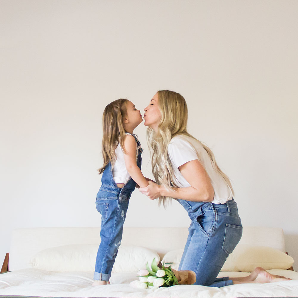my sweet little girl, matching me in overalls, kissing on our new avocado green mattress | thelovedesignedlife.com