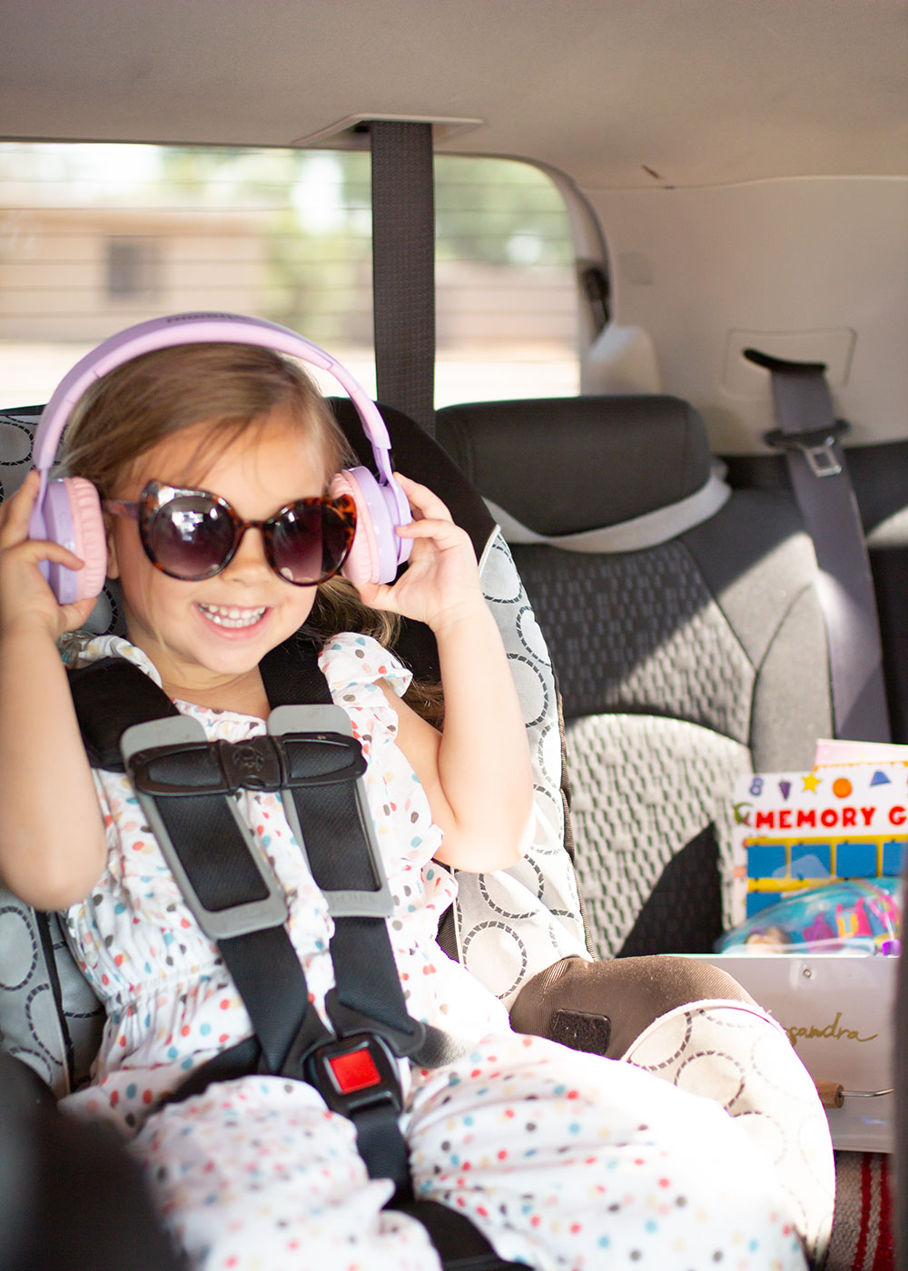 she was so excited for her new headphones! read more about this car hack on the blog | thelovedesignedlife.com #roadtrip #momhack