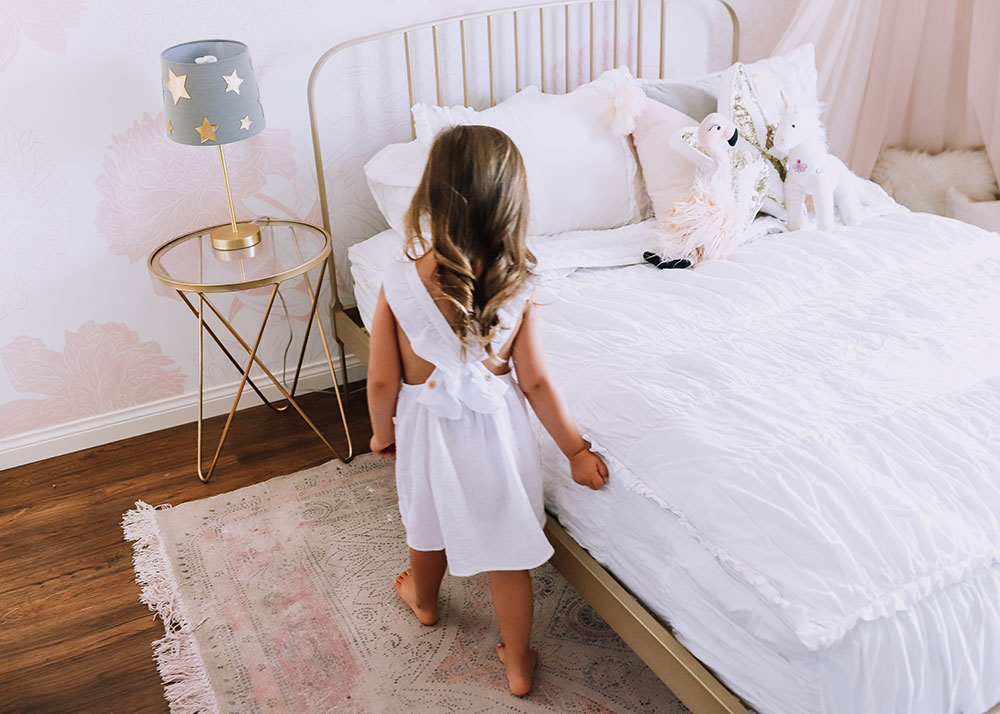 little girl making her bed to help with keeping the house clean | thelovedesignedlife.com #totalhomeprotection #zevo #girl's room