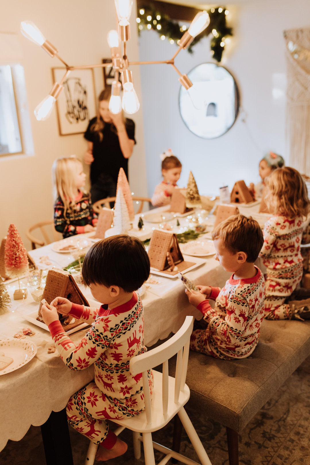 everyone ready to decorate their gingerbread houses and cookies at our simple party! | thelovedesigneldifecom #christmasjammies #gingerbreadshouses #christmaspartyidea #kidsparties