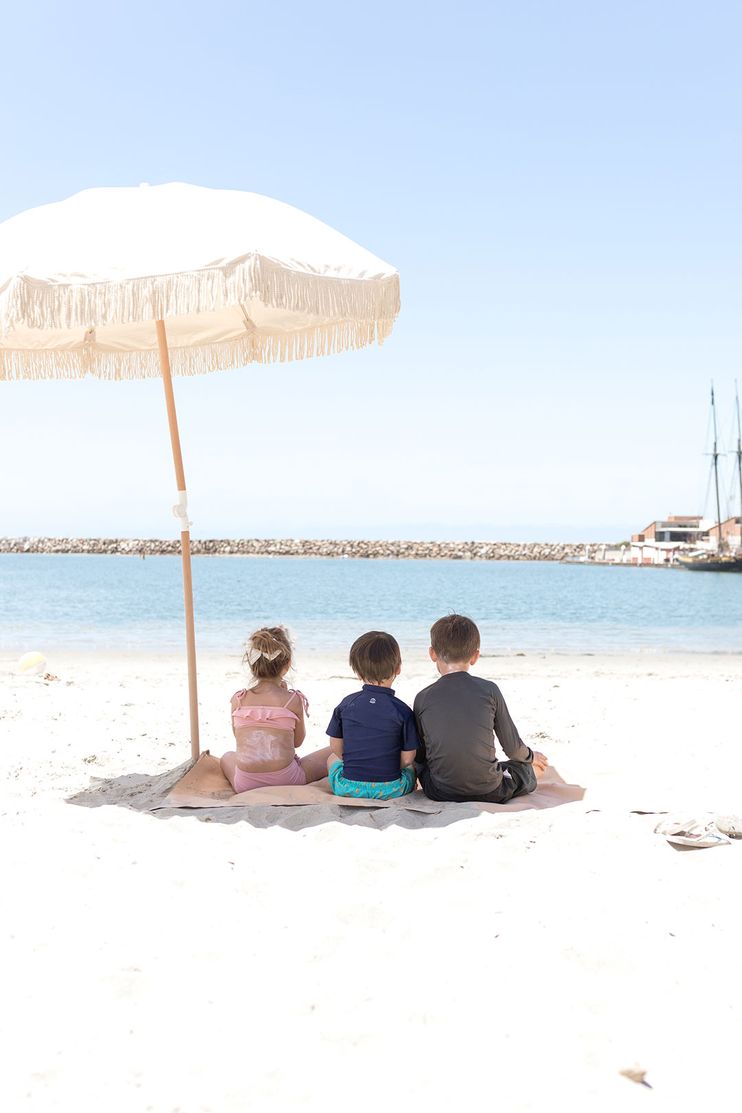 three kids sitting on the beach under an umbrella
