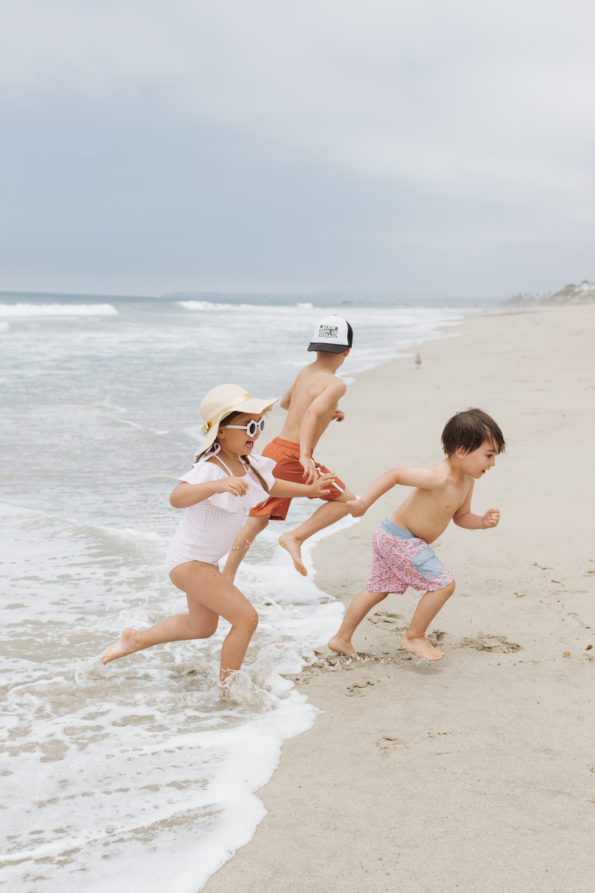 three kids running in the waves on the beach