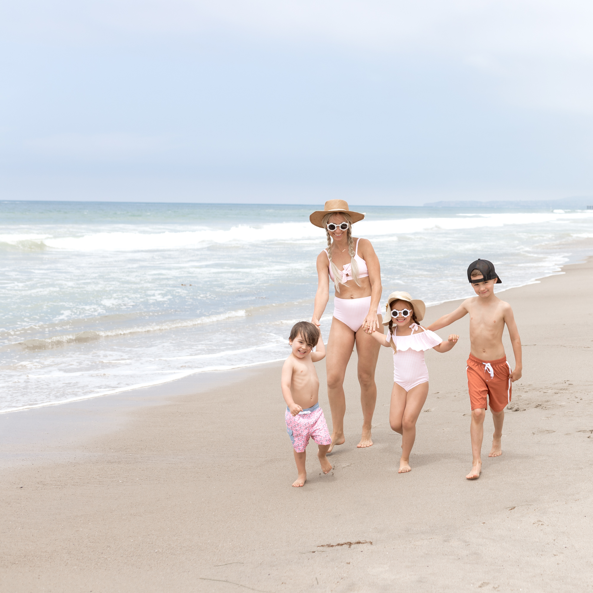 mom and three kids walking on the beach in swimsuits