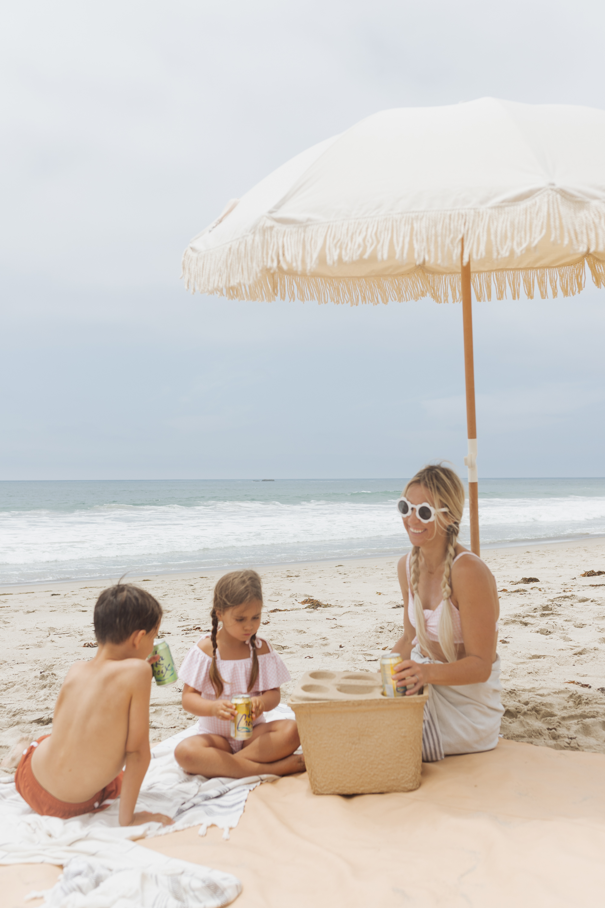 beach picnic under and umbrella with 3 people