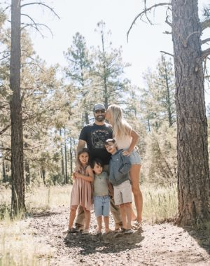 family of five standing in the mountain woods
