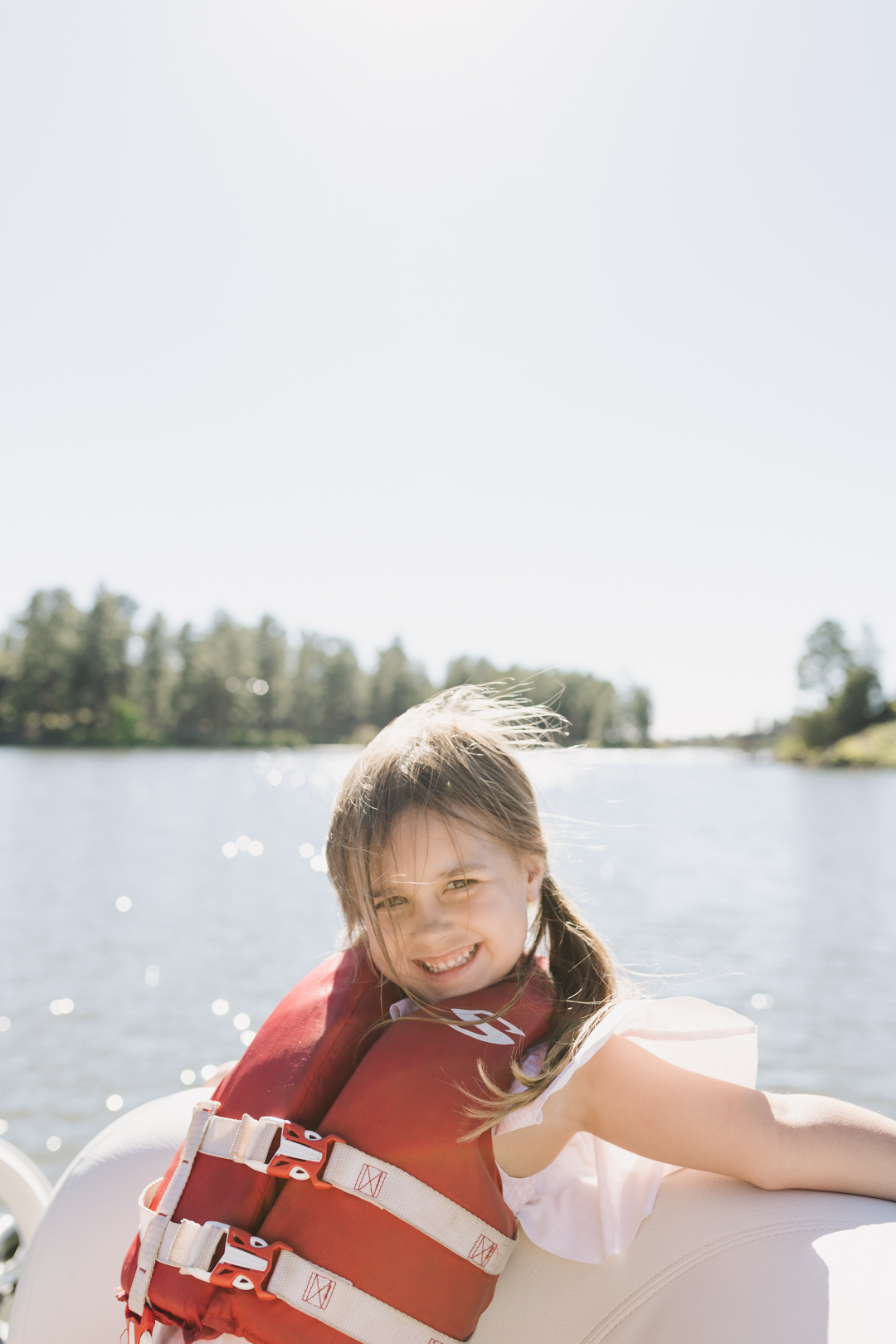 little girl with a life vest on a boat