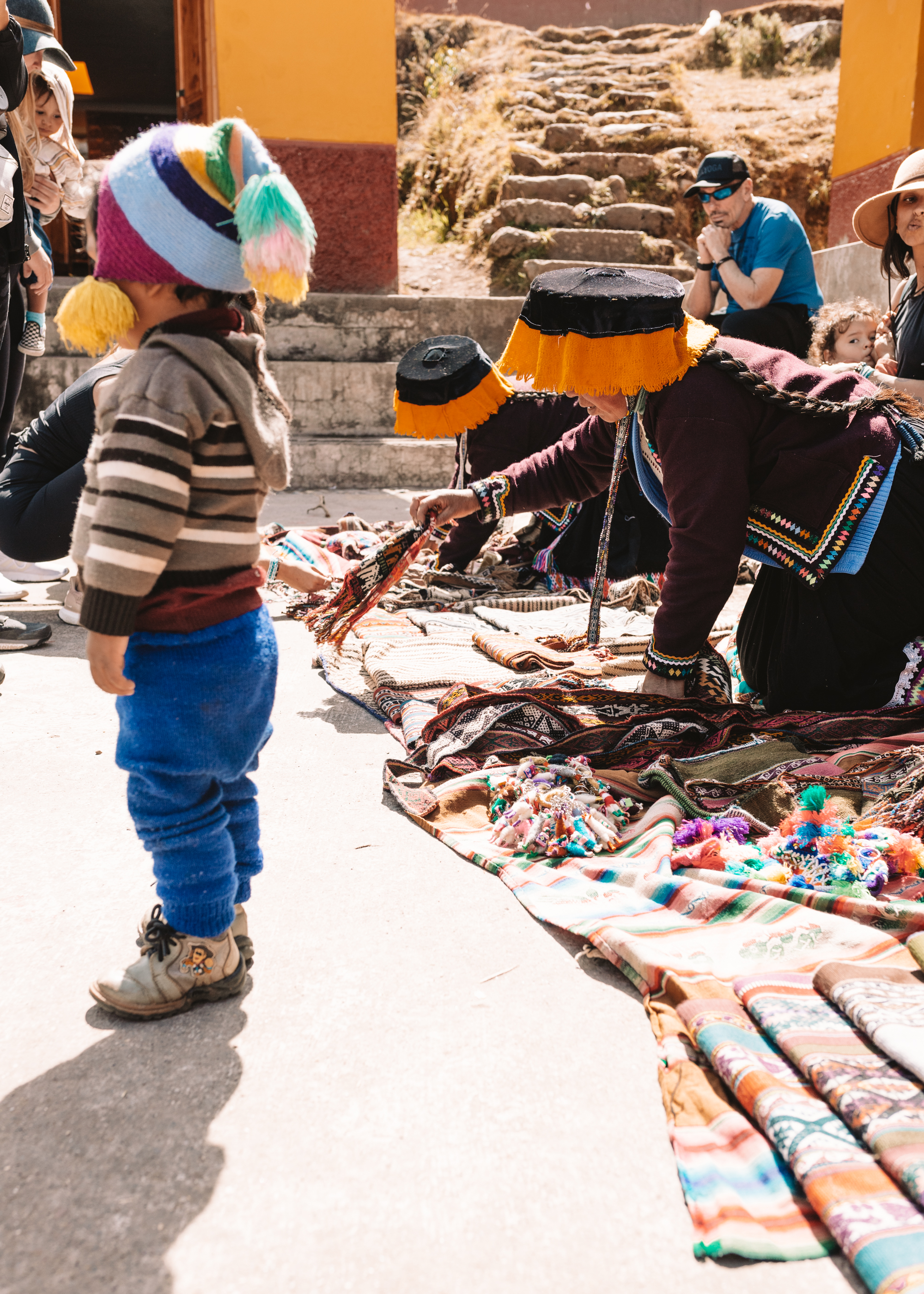 women laying out their wares to sell, while a sweet little toddler boy looks on. #peru #magicaljourney #travel