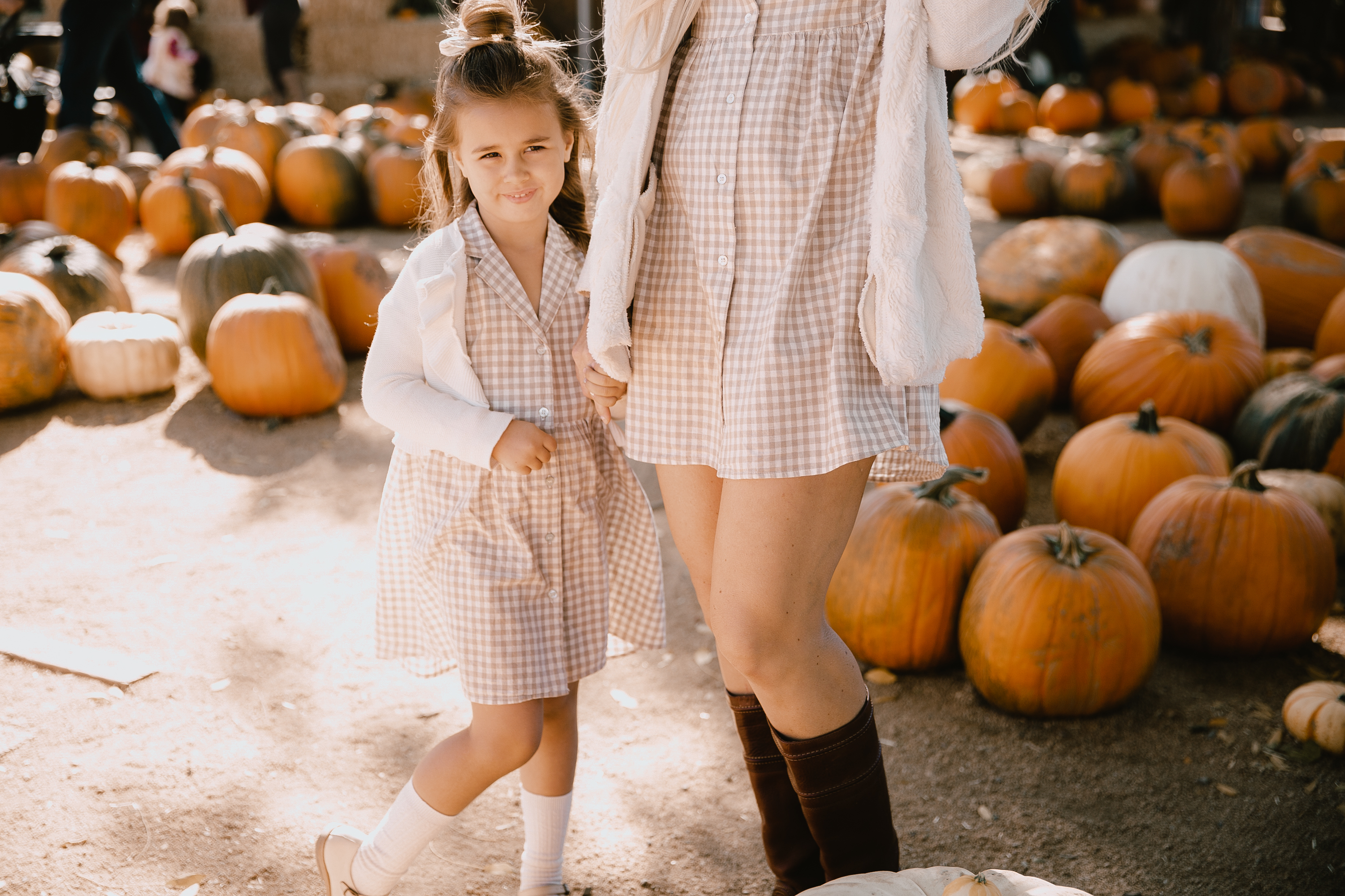 my cute little pumpkin in the patch, wearing our matching Rylee & Cru dresses from Bohemian Mama