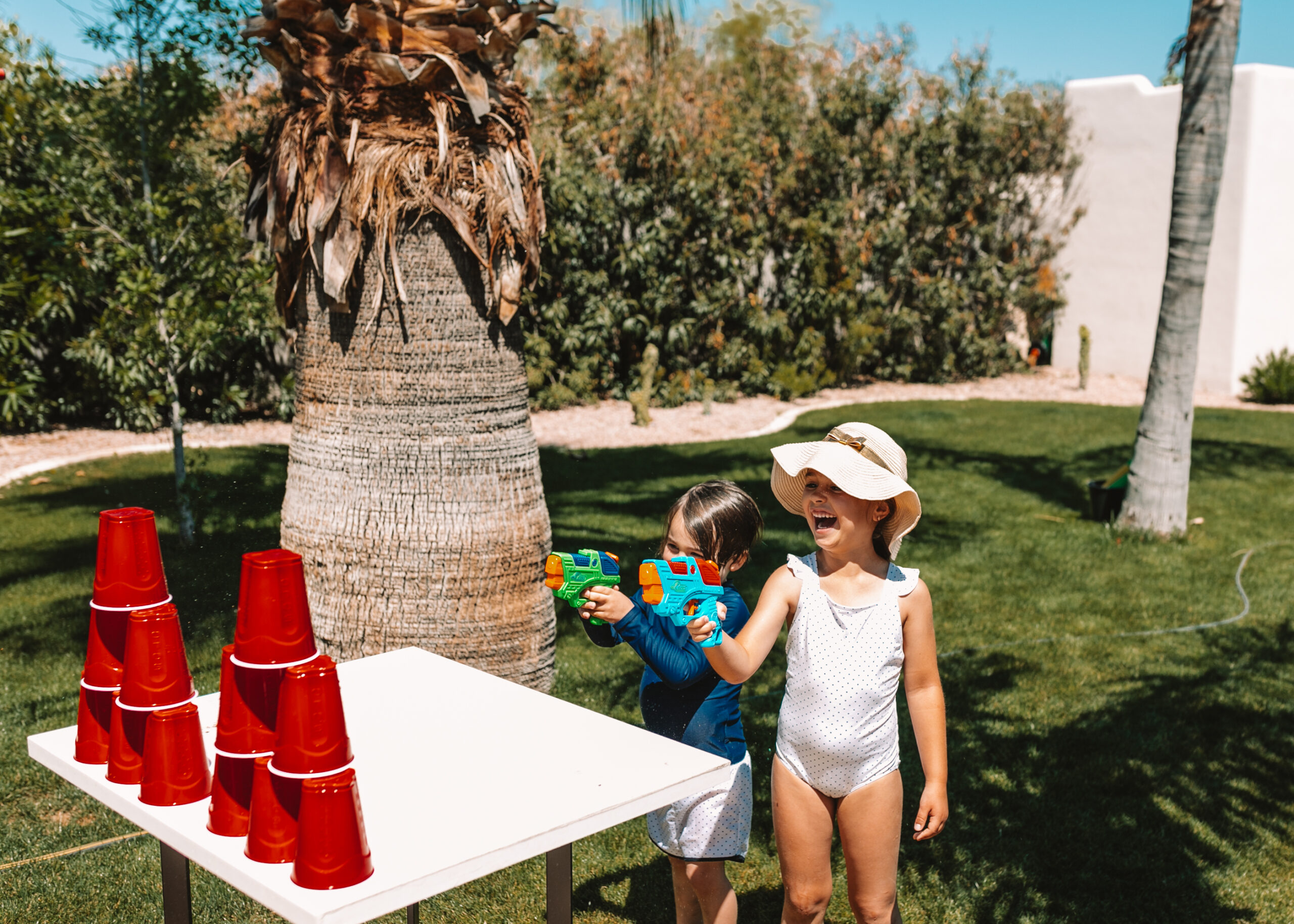 water gun cup shooting. set them up in a tower and see who can knock them all over first! #theldlhome #stayhome #watergunfun #backyardactivities