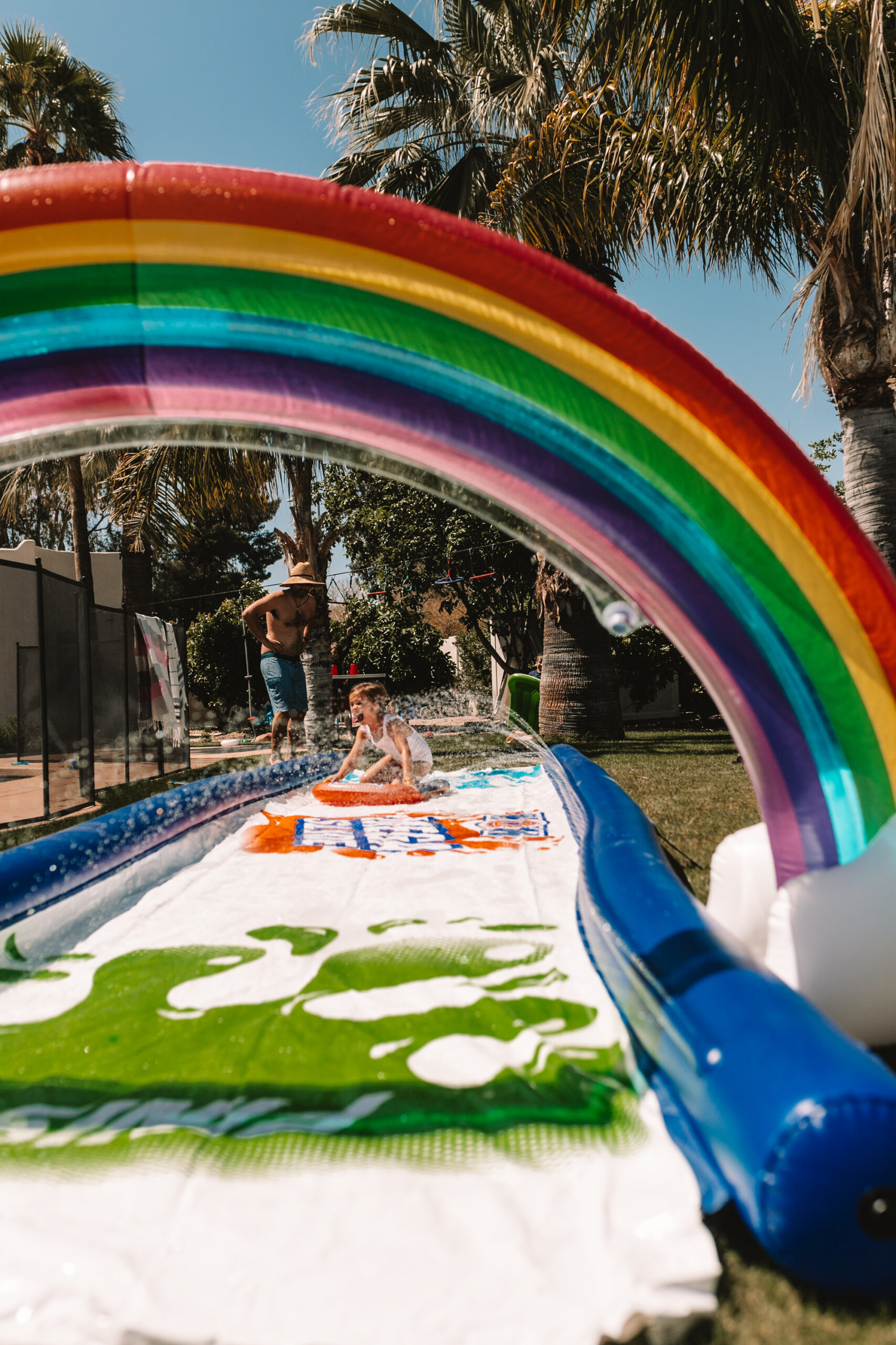 slip and slide with a rainbow sprinkler for our backyard field day! #slipandslide #backyardfun