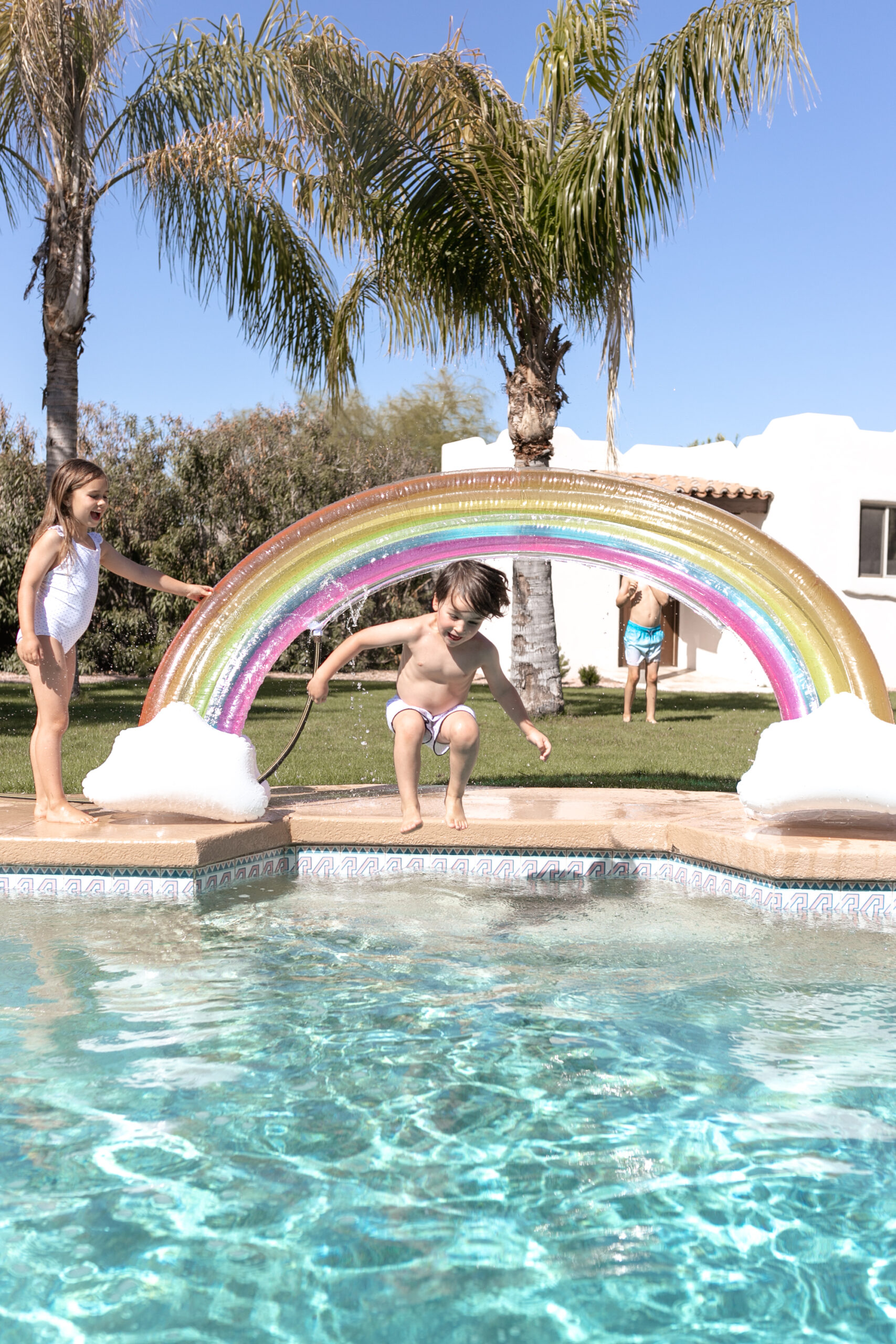 backyard pool time with our inflatable rainbow sprinkler. #backyardfun #childhood #summertime