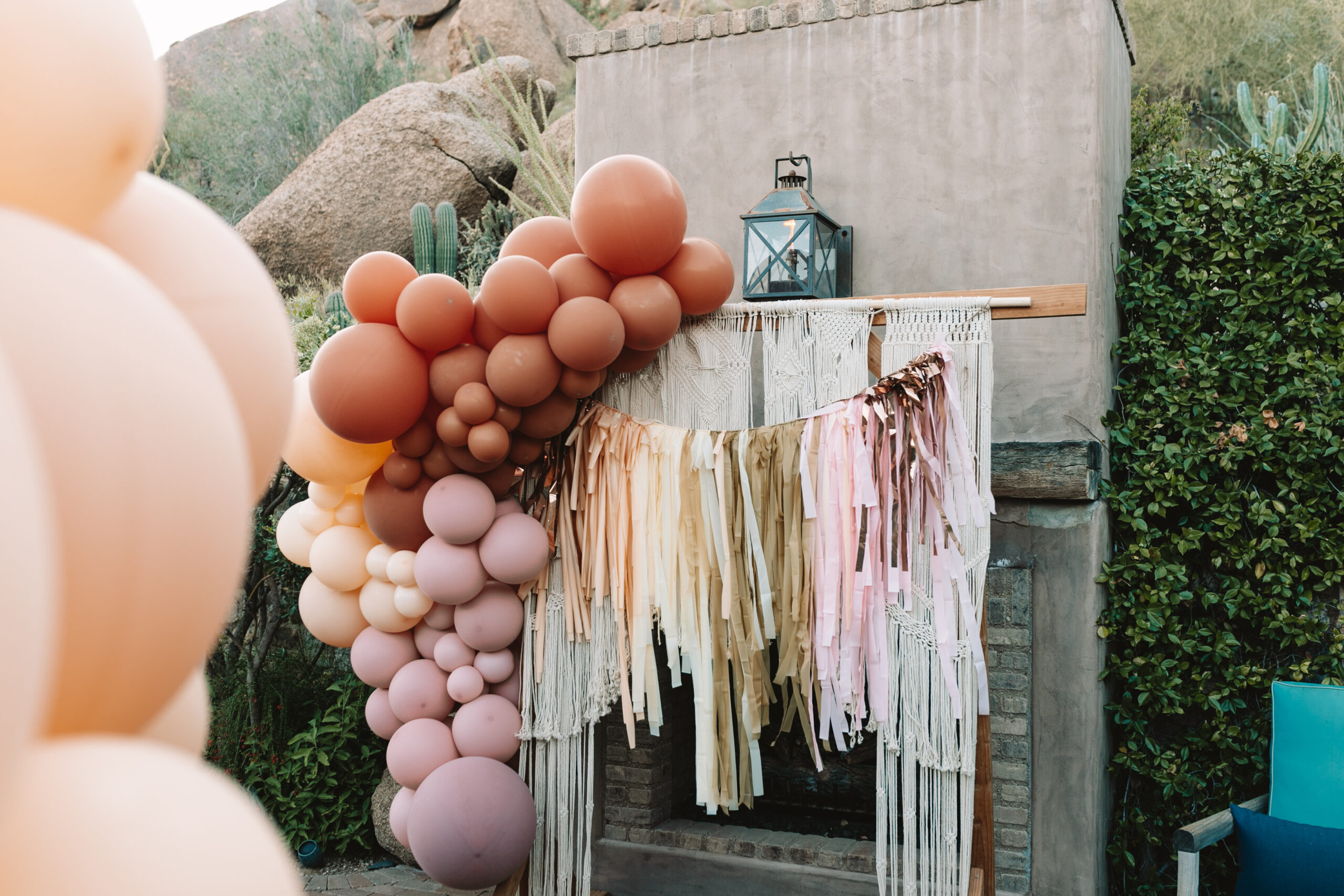 the prettiest decorations at our magical boho chic baby shower including this macrame hanging, balloon garland, and tissue tassel hanging #thelovedesignedlife #bohochickbabyshower #desertvibes #babyshowerideas