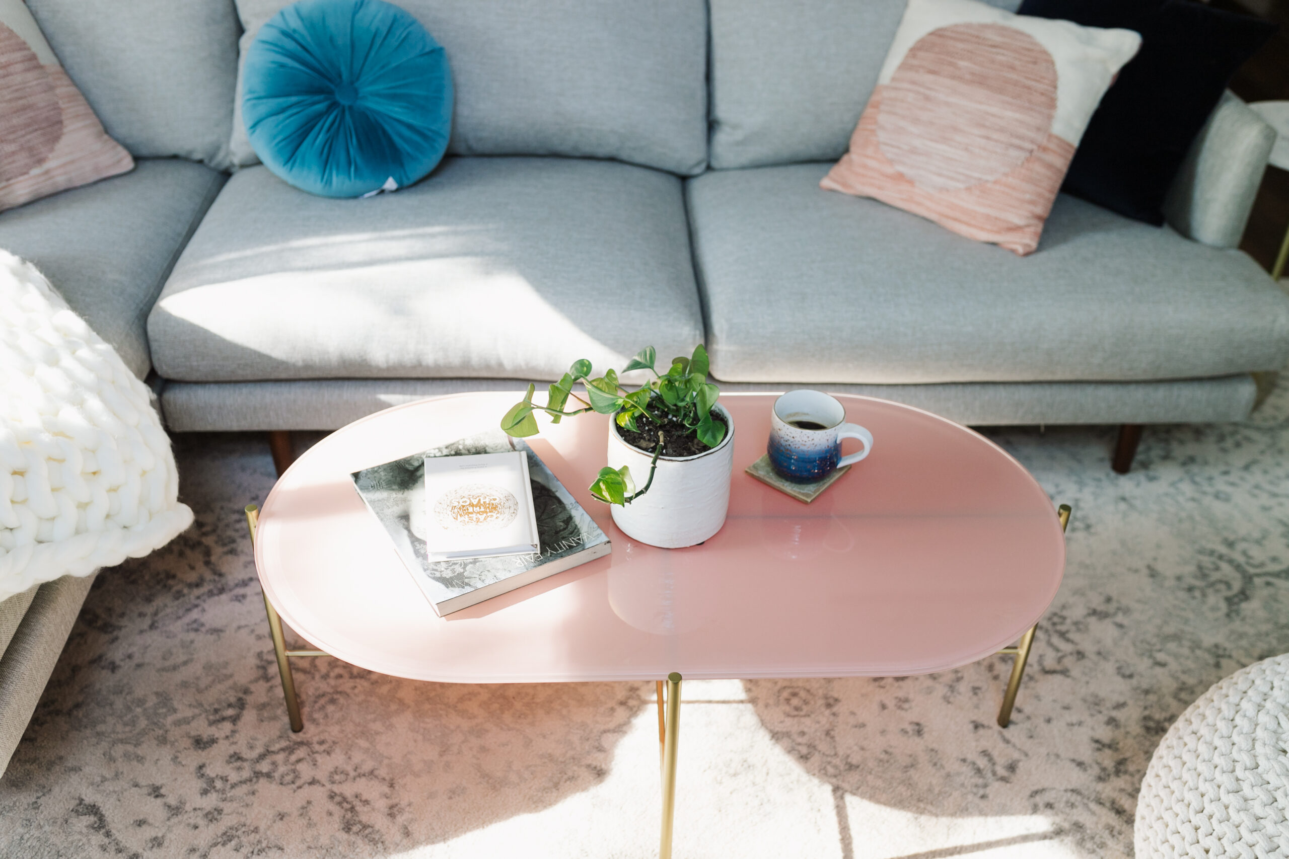 the gold legs and soft pink glass top add the perfect feminine touch to this modern mountain living room #theldlhome #ourarticle #silicusoblingcoffeetable #coffeetable #feminine #livingroom